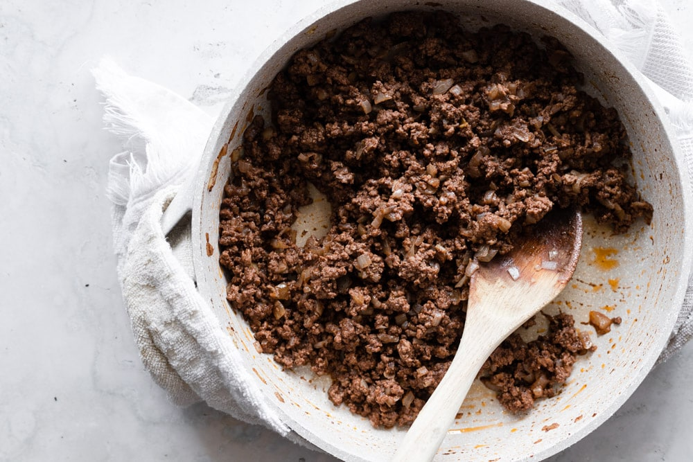 Cooked ground beef with onions in a large skillet with a wooden spoon and a towel underneath