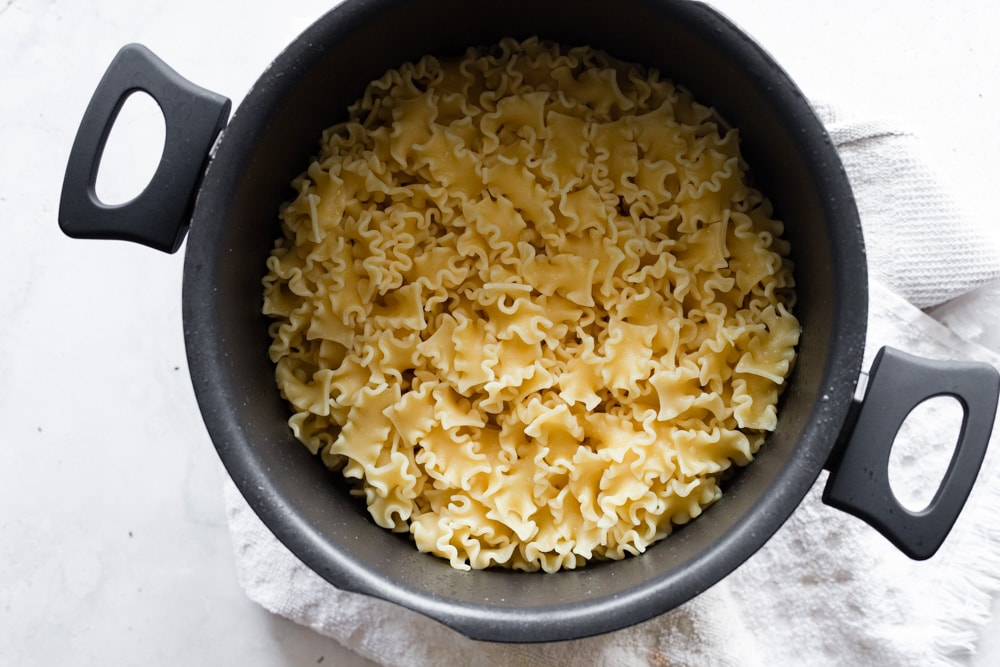 Cooked and drained pasta in a black pot with handles