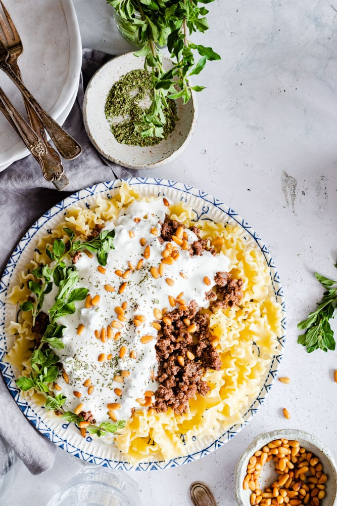 Arabic pasta served on a plate garnished with nuts and fresh herbs