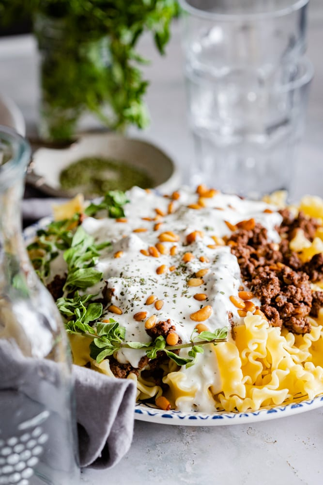 Arabic pasta served on a plate garnished with nuts and fresh herbs. A clear glass and jug is in the background and foreground