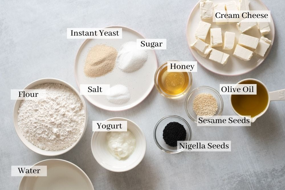 honeycomb bread ingredients which are flour, water, yogurt, salt, sugar, instant yeast, honey, nigella seeds, sesame seeds, olive oil, and cream cheese