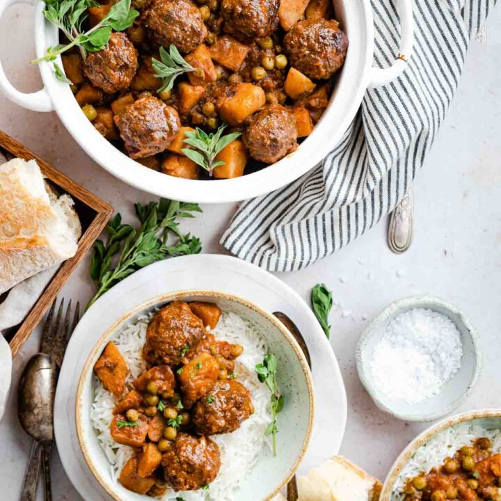 meatball stew with peas and potato served with a side of bread