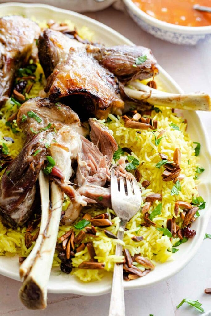 Quzi which is lamb shanks served over yellow rice with almonds and raisins