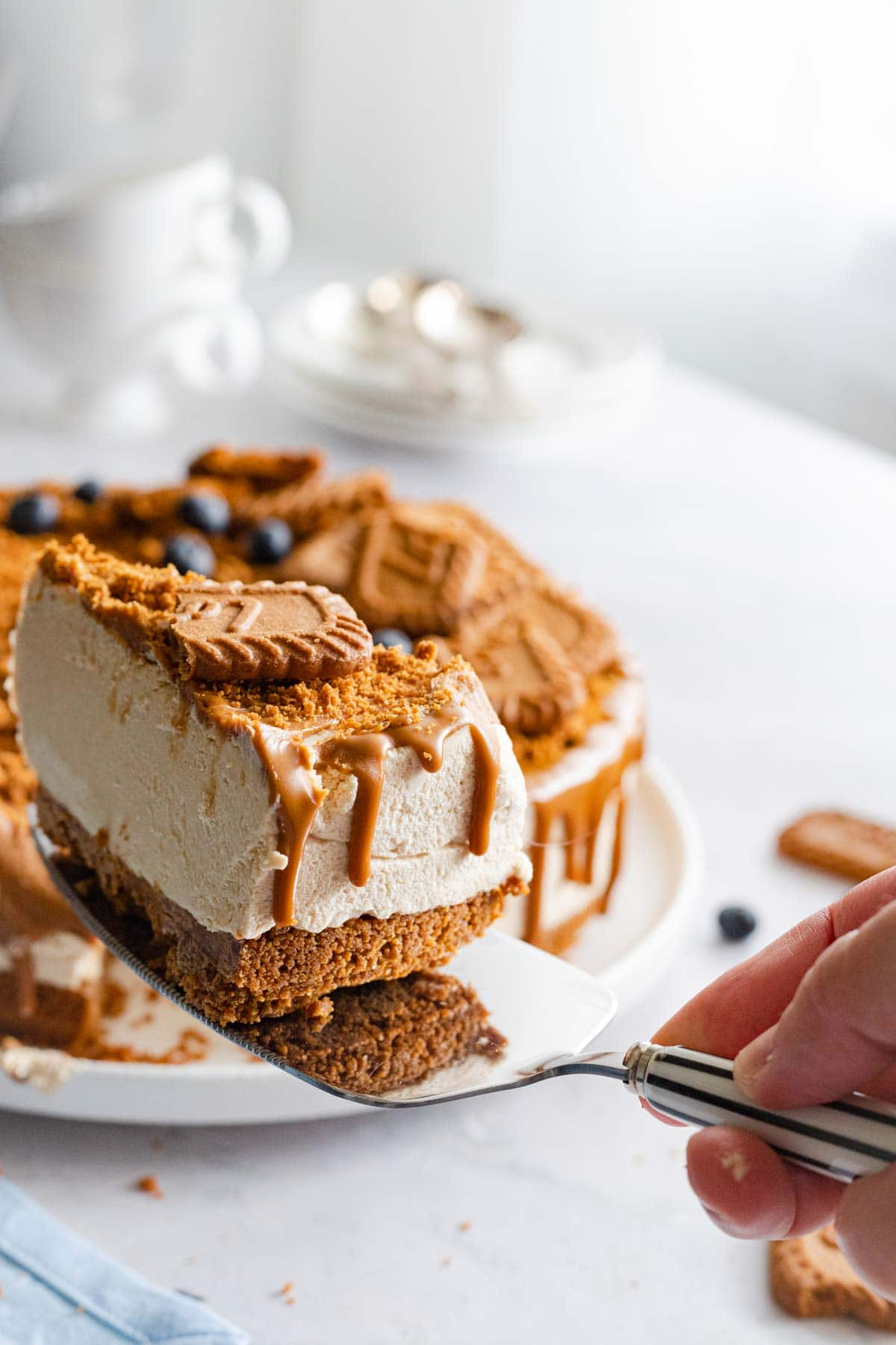 A slice of biscoff cheesecake being held up by a hand