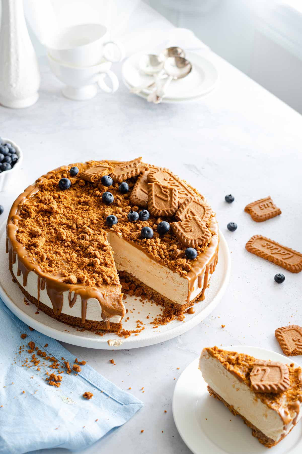 A biscoff cheesecake on a plate, garnished with biscoff cookies and blueberries