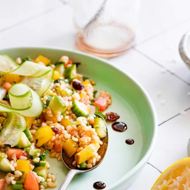 A colorful bulgur salad served on a plate with a spoon and a half cut lemon displayed beside it.