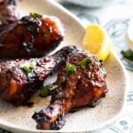 Chicken drumsticks glazed in pomegranate sauce served on a plate