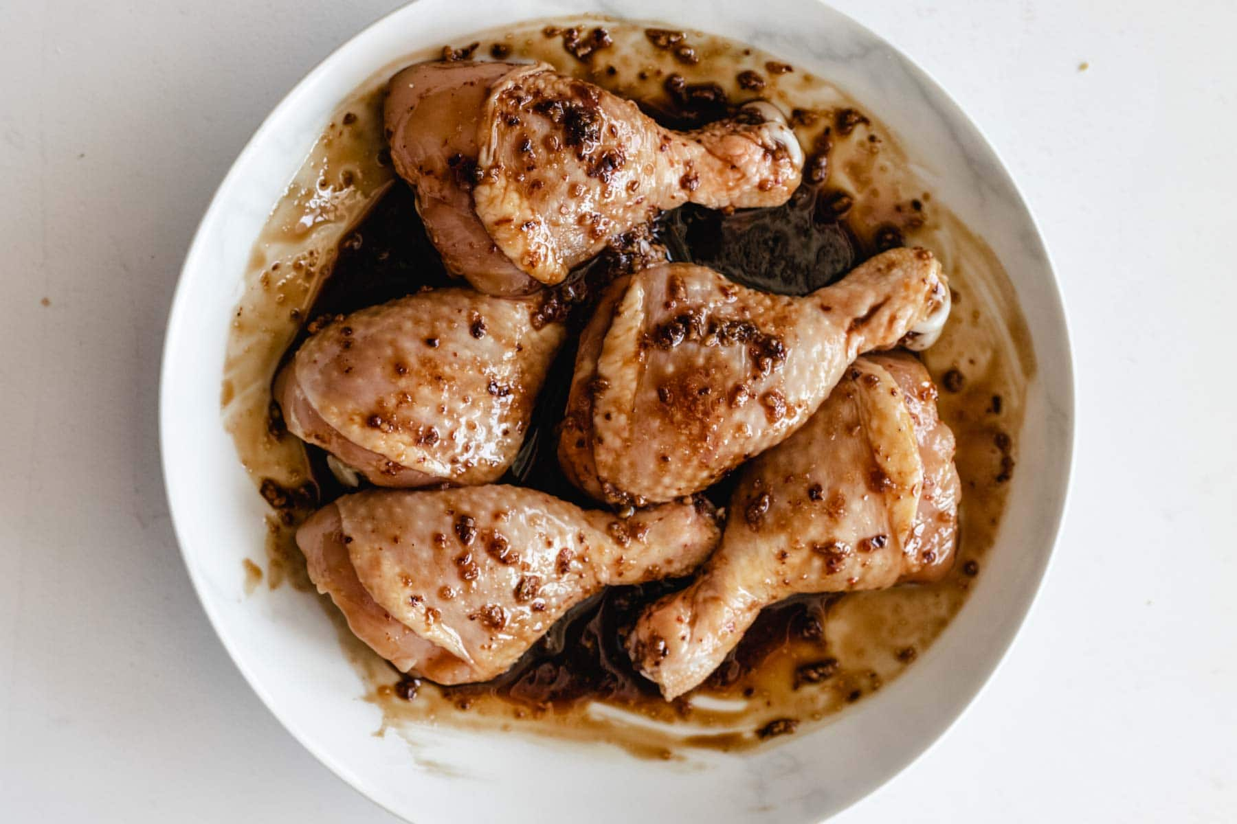 Marinated chicken drumsticks on a plate
