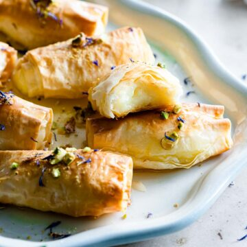 A plate decorated with several pieces of Znoud El Sit (Lady Fingers) drizzled with sugar syrup.