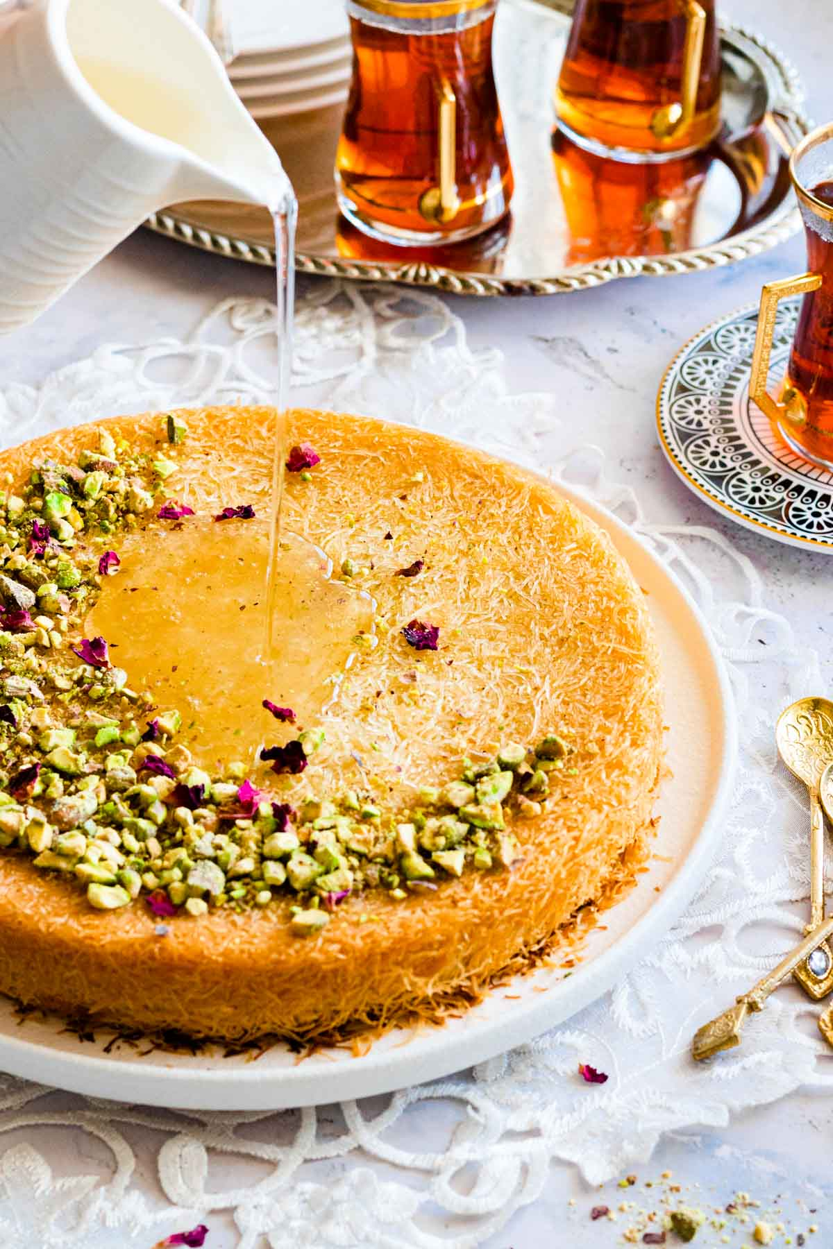 Golden phyllo dough pastry served on a plate garnished with nuts and drizzled with sugar syrup.