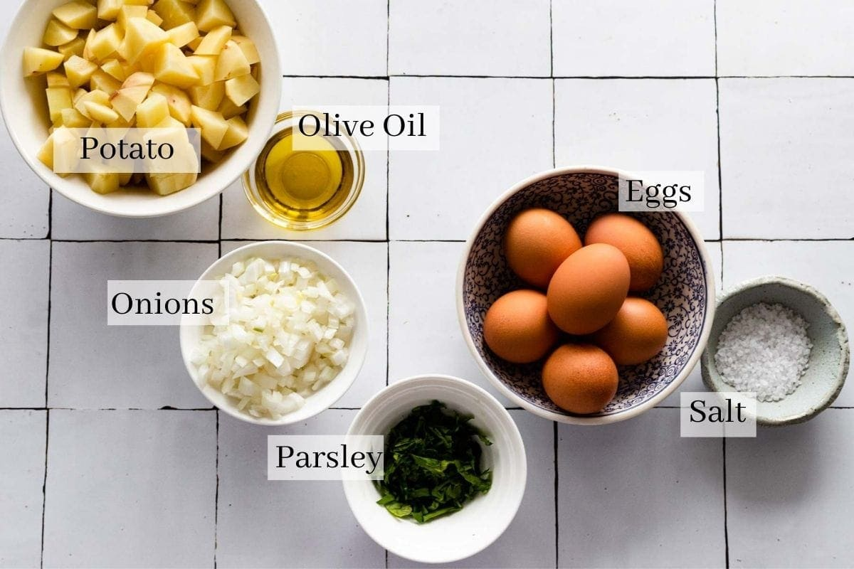 Ingredients for potato omelette which are cubed potatoes, onions, olive oil, parsley, eggs and salt