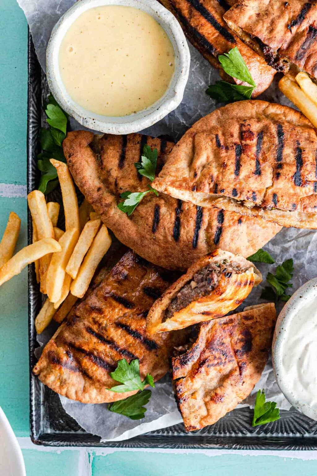 Pita bread stuffed with ground beef and grilled, served on a tray with fries and sauce