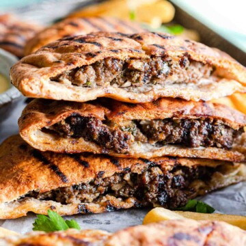 Pita stuffed with ground beef and grilled, stacked in a pile of three