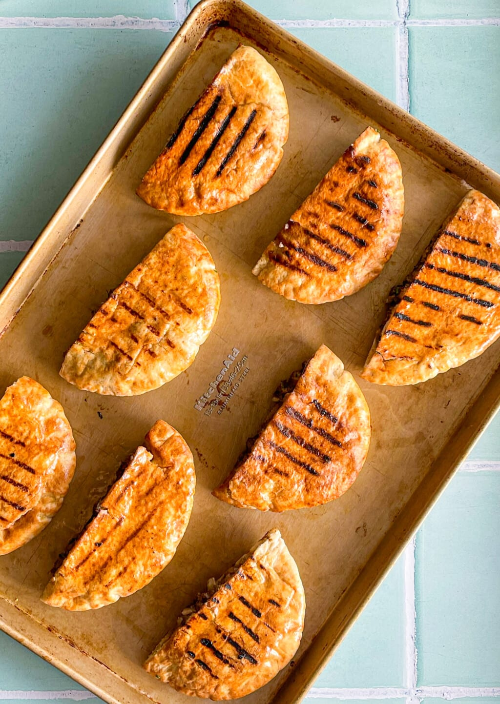 Grilled pita stuffed with ground beef on a baking sheet