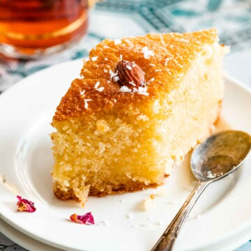 A small slice of Namoura cake served on a plate garnished with almond and shredded coconut