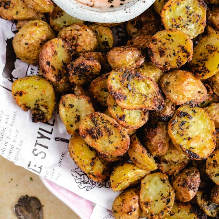 roasted potatoes in a serving platter with a dipping sauce